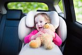 image of car ride  - Cute curly laughing and talking toddler girl playing with a toy bear enjoying a family vacation car ride in a modern safe vehicle sitting in a baby seat with belt having fun watching out of the window - JPG