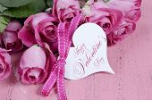 Pink Roses On Pink Wood Background Closeup With Happy Valentines Day Heart Shape Gift Tag.