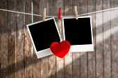Two Blank Instant Photos Hanging On The Clothesline