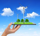 Hand holding digital tablet with a wind turbines and trees . Green energy concept.