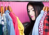 Young attractive surprised woman searching for clothing in a closet