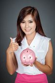 Beautiful Asian Girl Thumbs Up With A Pink Pig Money Box