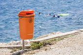 Orange trash bin near the sea beach.