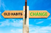 image of  habits  - Wooden signpost with two opposite arrows over clear blue sky Old Habits versus Change messages Lifestyle change conceptual image - JPG
