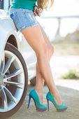 Beautiful female legs near the new car.