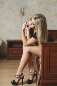Beautiful blonde in fashionable shoes with high heels sitting on the bed.