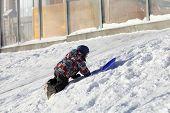 Boy Climbing On A Snowy Hill