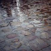 Cobblestone Pavement In Rainy Day - Retro Filter. Wet Paving Stone With Puddles.