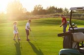 foto of clubbing  - Casual kids at a golf field holding golf clubs studying with trainer. Sunset