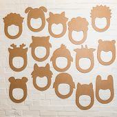 Set Of Cardboard Masks On A White Brick Wall.