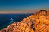 orange glowing rocks of mountain peak with cross at sunset