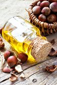 Bottle Of  Healthy Nut Oil And Basket With Hazelnuts On Old Kitchen Table.