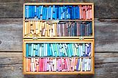 Set Of Multicolored Pastel Crayons In Open Wooden Artist Box On Rustic Wooden Desk, Top View.