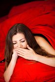 The woman lying on a bed with red bed linen.