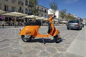 stock photo of vespa  - Orange Vespa parked on the sidewalk - JPG