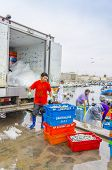 PISCO, PERU, MAY 21, 2014: Man loads boxes of freshly caught fish into a refrigerated truck in fishermen's wharf of San Andres.