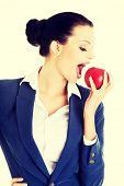 Young healthy business woman eating red apple.