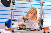 girl student makes the item on the 3D printer