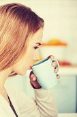 Beautiful smiling woman is drinking hot drink.