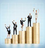 Businessmen keeping golden cup on coins ladder. Concept of success in teamwork