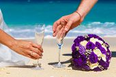 Wedding Bouquet And Two Glasses Of Champagne On The Sand. Male And Female Hands With Wedding Rings