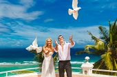 The Happy Bride And Groom With White Doves On A Tropical Beach Under Palm Trees.