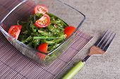 Seaweed salad with slices of cherry tomato in glass bowl on bamboo mat and burlap cloth background