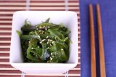 Seaweed salad in bowl with sticks on bamboo mat and color table background