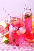 Pink lemonade in glasses and bottle on bright background