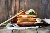 Stack of pancakes with mint, honey and slices of banana on rustic wooden background