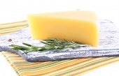 Chunk of Parmesan cheese on wooden cutting board with sprig of rosemary on napkin isolated on white