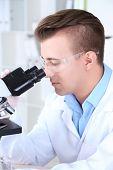 Male scientist using microscope in laboratory
