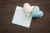 stock photo of wood craft  - Blue hearts handmade crafts from polka dot cotton cloth with blank notepad place on wood background with vignette wedding and anniversary symbol - JPG
