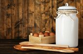 Milk can with eggs and spoons on rustic wooden background