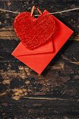 Red  heart and envelop  hanging on the clothesline. On old wood background