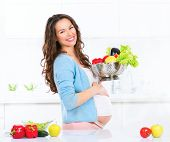 Pregnant Young Woman Cooking vegetables. Healthy Food - Vegetable Salad. Diet. Dieting Concept. Healthy Lifestyle. Cooking At Home. Prepare Food