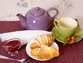 Breakfast with fresh croissants, cup of tea and jam