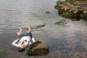 picture of accident victim  - View of a young woman washed up on rocks at the edge of a river - JPG