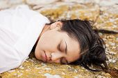 pic of accident victim  - View of a young woman washed up on rocks at the edge of a river possible boating accident victim - JPG