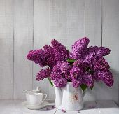 Cup of coffee and Lilac Bouquet in ceramic jug against a white wooden board.