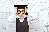 Shocked schoolgirl in big glasses and academic hat stands at the blackboard and holds her head. Educational concept.
