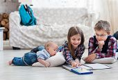 foto of pry  - Brother and sister drawing with crayons in living room with baby brother - JPG