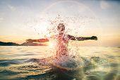 picture of beach sunset  - Man splashing water during summer holidays  - JPG