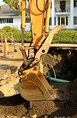 picture of track-hoe  - a large track hoe exchavator at the repair work following a broken water main leak from a fire hydrant base - JPG