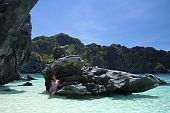 stock photo of filipina  - filipina woman stading by sharp jagged rock in karst surrounded lagoon in el nido palawan island in the philippines - JPG