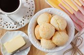 picture of brazilian food  - Brazilian snack pao de queijo (cheese bread) on white plate with cheese ham butter cup of coffee on wooden table. Selective focus ** Note: Shallow depth of field - JPG