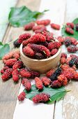 pic of mulberry  - Fresh mulberry in wooden bowl on wooden background - JPG