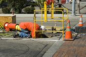 stock photo of manhole  - blue collar worker putting cables and wires underground thru manhole cover - JPG