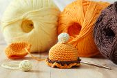 stock photo of thread-making  - Making of handmade colorful crochet toys sweets with skein on wooden table - JPG