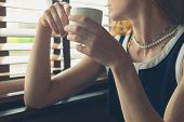 stock photo of diners  - A young woman is having a cup of coffee by the window in a diner - JPG